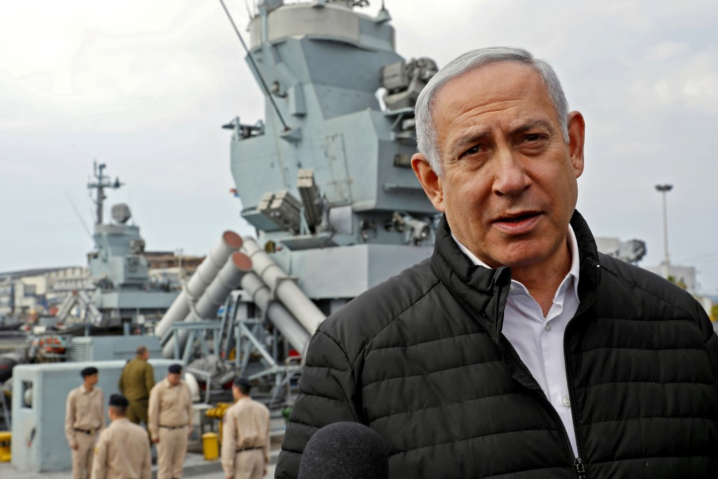 Israeli Prime Minister Benjamin Netanyahu, right, speaks with journalists during a visit to inspect a naval Iron Dome defence system, installed on a S...