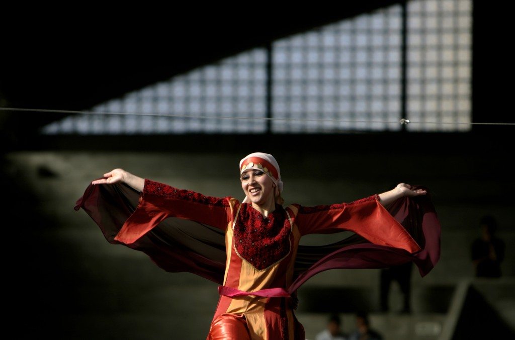 FILE - In this April 29, 2007 file photo, a Palestinian woman wearing a Palestinian dress with traditional embroidery performs a folk dance known as D...