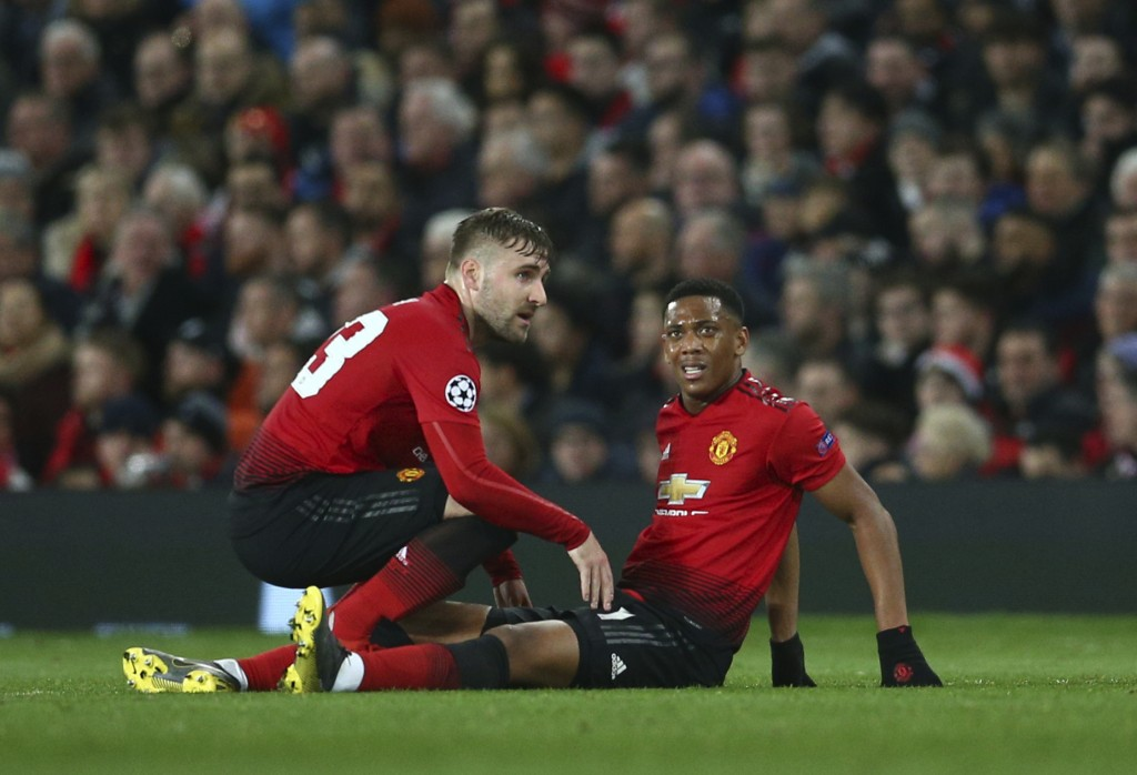 Manchester United's Luke Shaw, left, speaks to Manchester United's Anthony Martial who is injured during the Champions League round of 16 soccer match...