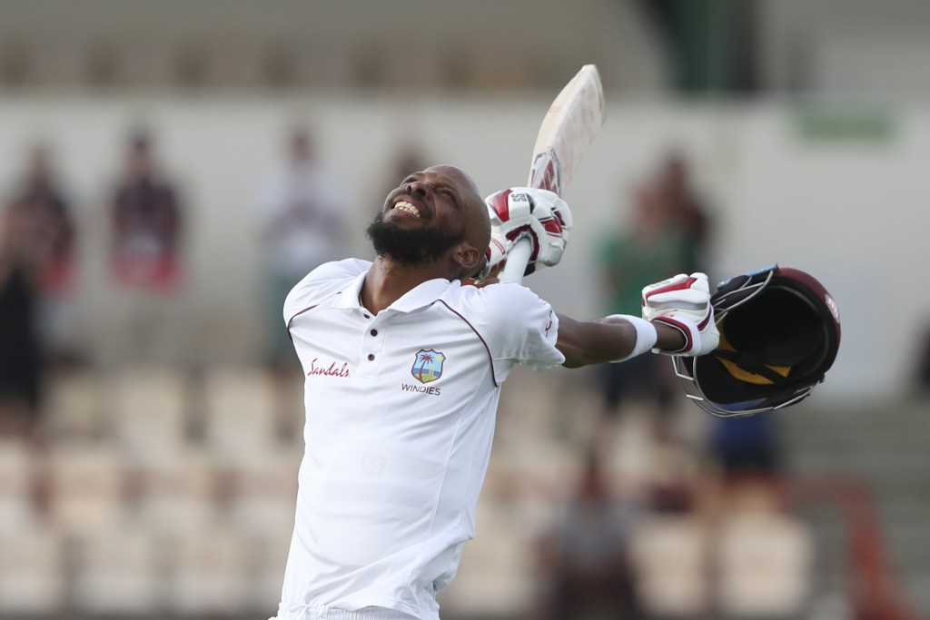 West Indies' Roston Chase celebrates after he scored a century against England during day four of the third cricket Test match at the Daren Sammy Cric...