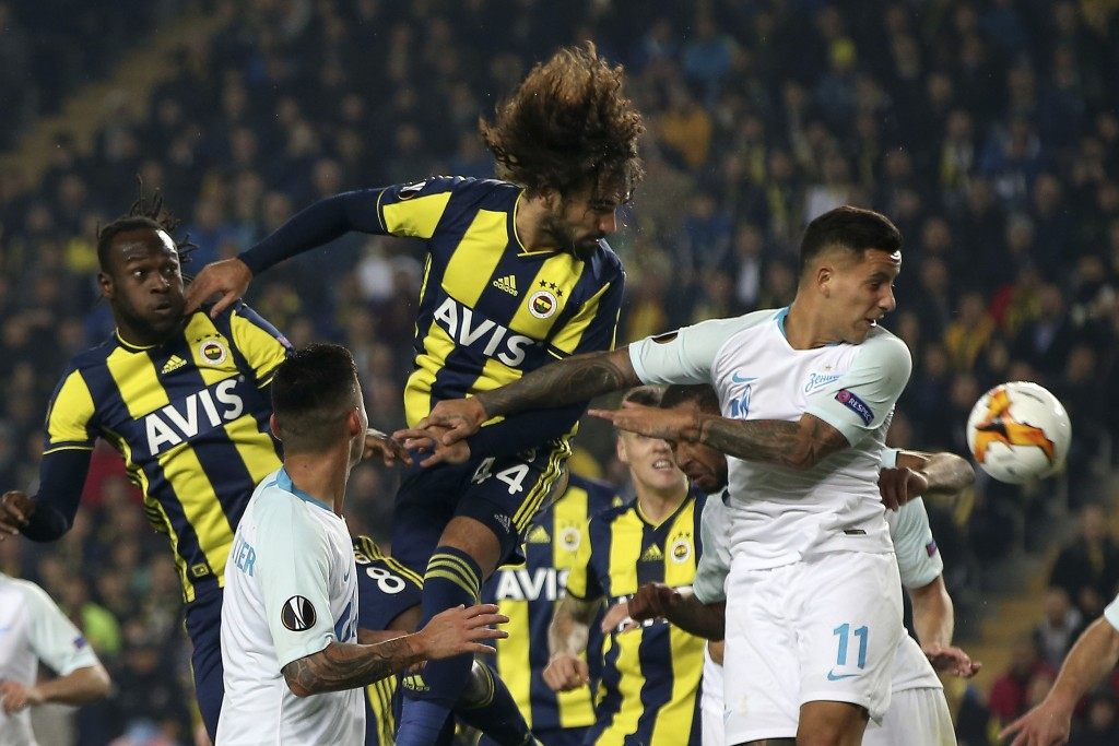 Fenerbahce's Sadık Ciftpınar, center, jumps for the ball with Zenit St. Petersburg's Sebastian Drisussi, right, during the Europa League round of 32 s...