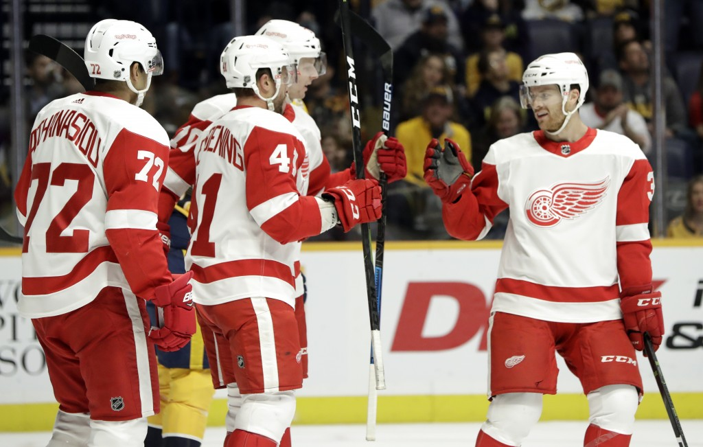Detroit Red Wings center Luke Glendening (41) celebrates with Nick Jensen (3) and Andreas Athanasiou (72) after Glendening scored a goal against the N