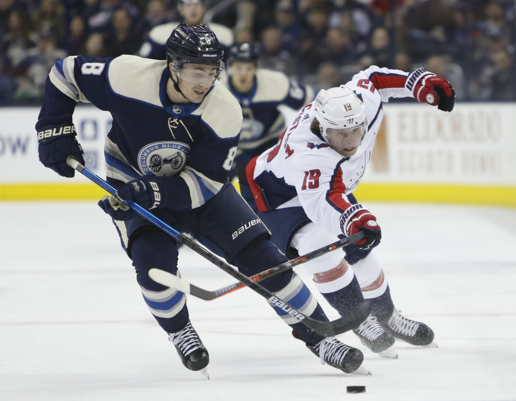 Columbus Blue Jackets' Zach Werenski, left, tries to control the puck as Washington Capitals' Nicklas Backstrom, of Sweden, defends during the first p