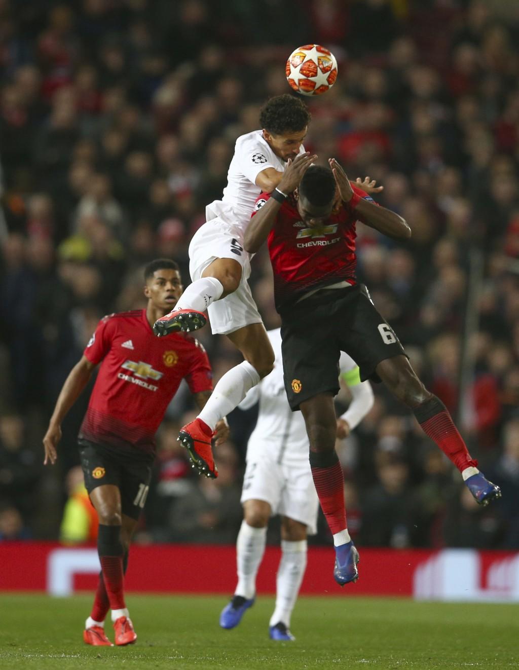 Manchester United's Paul Pogba, right is fouled as he leaps for the ball by Paris Saint Germain's Marcos Marquinhos during the Champions League round ...