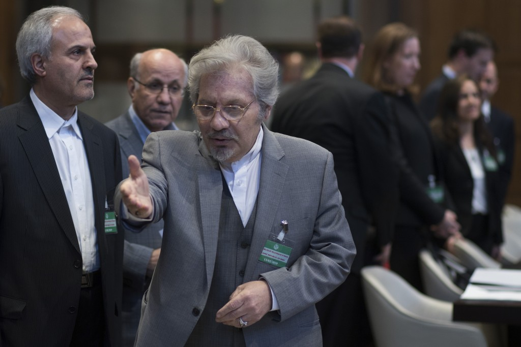 Mohsen Mohebi, agent for the Islamic Republic of Iran, gestures to his delegation to take their seats, as the U.S. delegation is seen in the backgroun