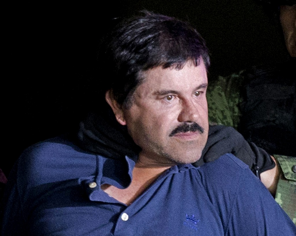 """FILE - In this Jan. 8, 2016 file photo, drug lord Joaquin """"El Chapo"""" Guzman is made to face the media in Mexico City as he is escorted by Mexican sold"""