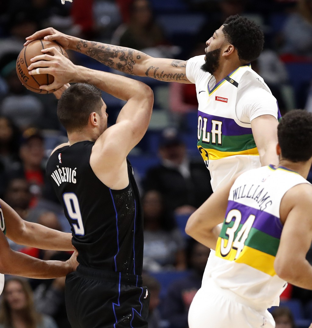 Orlando Magic center Nikola Vucevic (9) is blocked by New Orleans Pelicans forward Anthony Davis (23) during the first half of an NBA basketball game ...