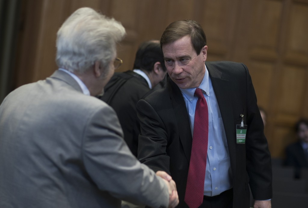 Mohsen Mohebi, left, agent for the Islamic Republic of Iran, greets Richard Visek, agent for the U.S.A, as they wait for judges to enter the Internati
