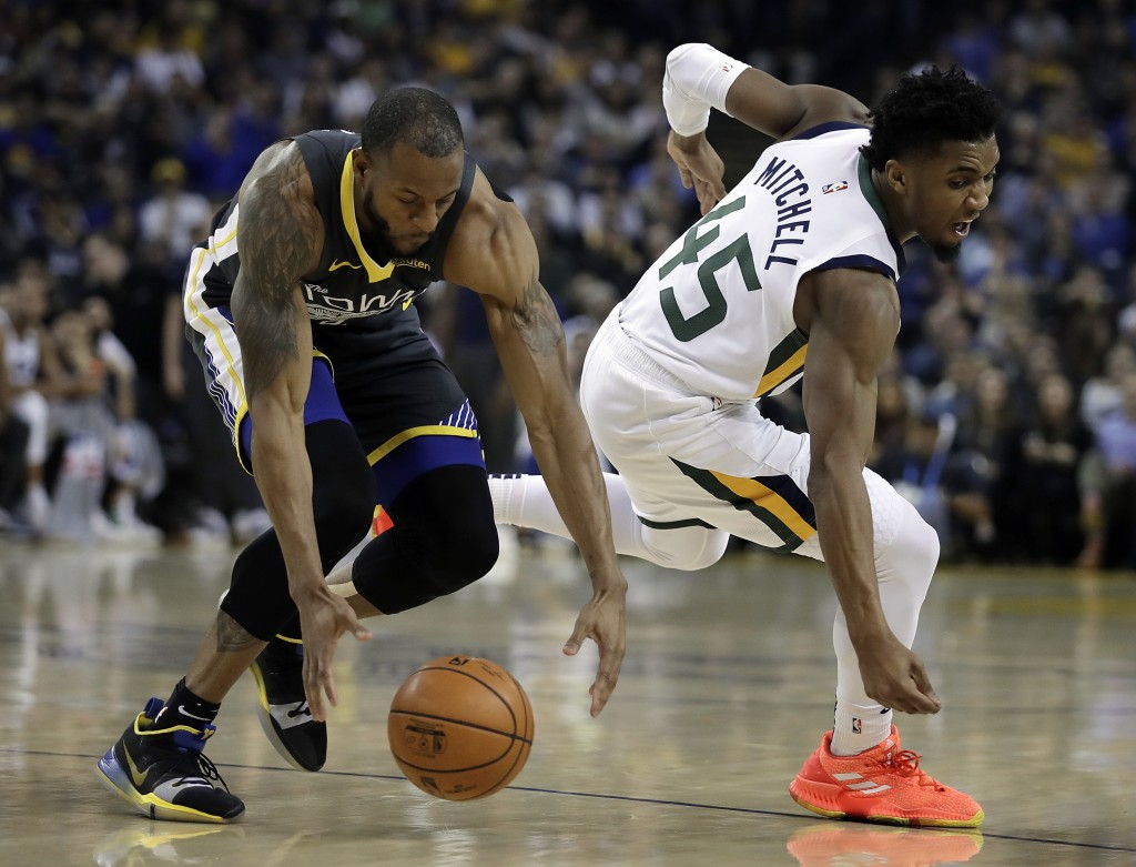 Golden State Warriors' Andre Iguodala, left, and Utah Jazz guard Donovan Mitchell chase a loose ball during the first half of an NBA basketball game,
