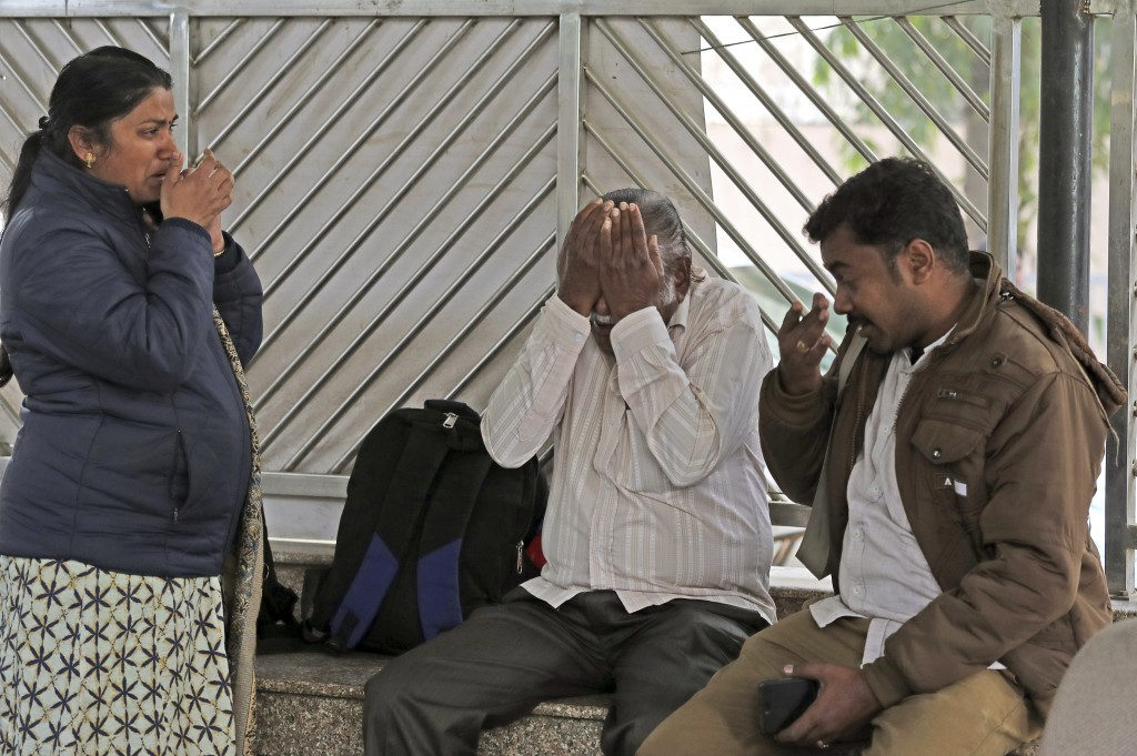 Relatives grieve outside a mortuary as they wait to receive the body of a person who died in hotel fire early Tuesday morning in New Delhi, India, Wed...