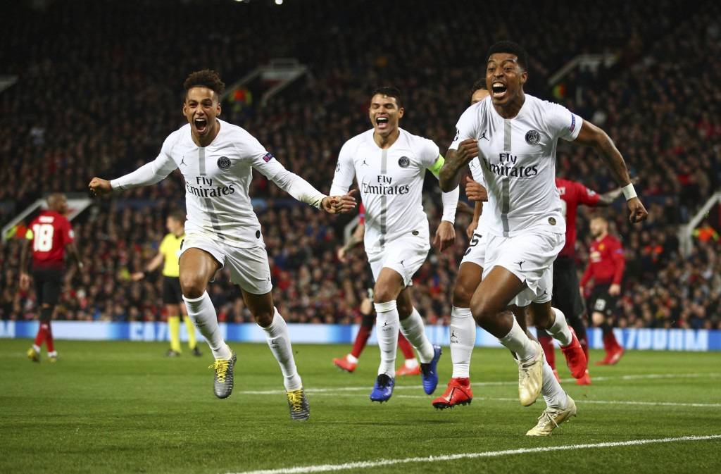 Paris Saint Germain's Presnel Kimpembe, right, celebrates after scoring the opening goal the game during the Champions League round of 16 soccer match