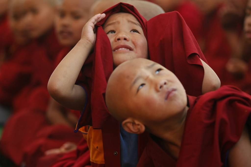 In this Wednesday, Feb. 13, 2019, file photo, young monks get distracted by a drone as they watch a traditional dance during Cham dance festival as pa...