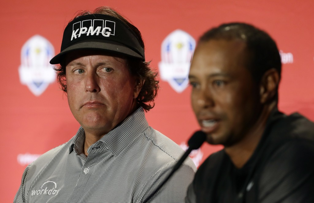 FILE - In this Sept. 4, 2018, file photo, Phil Mickelson, left, listens to Tiger Woods speak during a news conference where they were announced as cap...