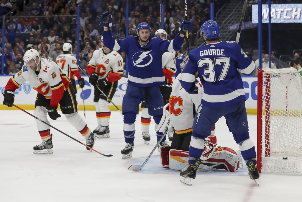 Tampa Bay Lightning's Yanni Gourde (37) and Anthony Cirelli celebrate a goal as Calgary Flames goaltender David Rittich, of the Czech Republic, and Ma...