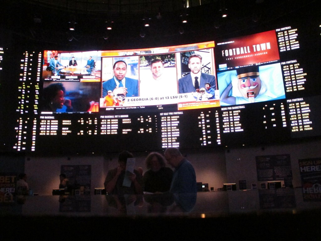 FILE -  In this Oct. 12, 2018, file photo, people sit inside a sports betting lounge at the Ocean Resort Casino in Atlantic City N.J. Now, for the fir