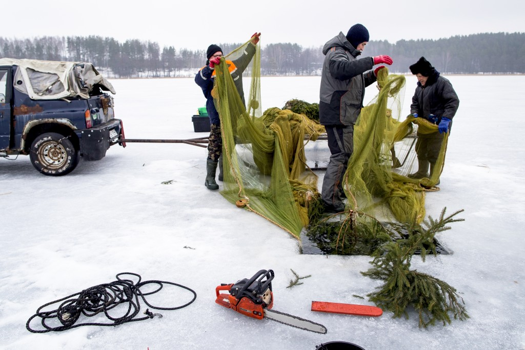 In this photo taken on Saturday, Feb. 9, 2019, fishermen prepare a net at a hole during a traditional winter smelt fish festival on Lusiai lake some 1