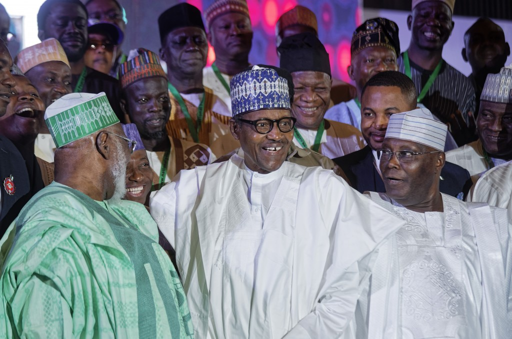 Incumbent President Muhammadu Buhari, center, and opposition presidential candidate Atiku Abubakar, right, stand for a group photo with other candidat...