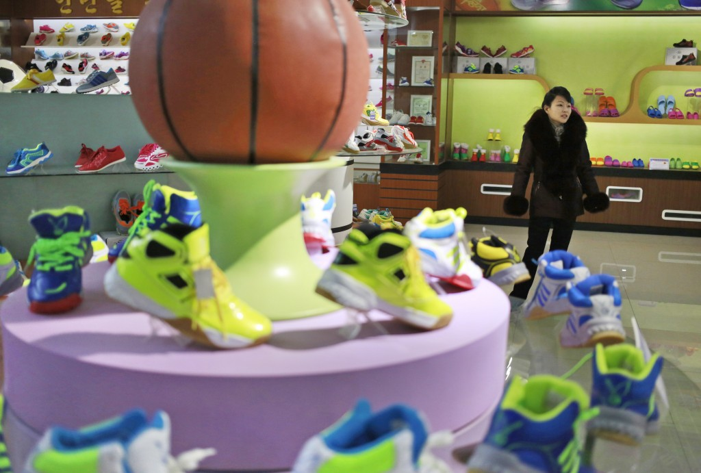In this Friday, Feb. 1, 2019, photo, a guide stands near a basketball shoe display in a product exhibition room at the Ryuwon Shoe Factory that specia...