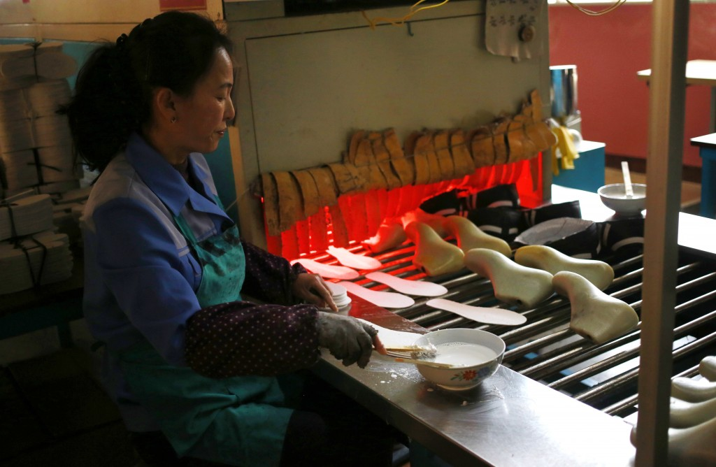 In this Friday, Feb. 1, 2019, photo, a worker tend to her station at Ryuwon Shoe Factory that specializes in sports footwear, in Pyongyang, North Kore...