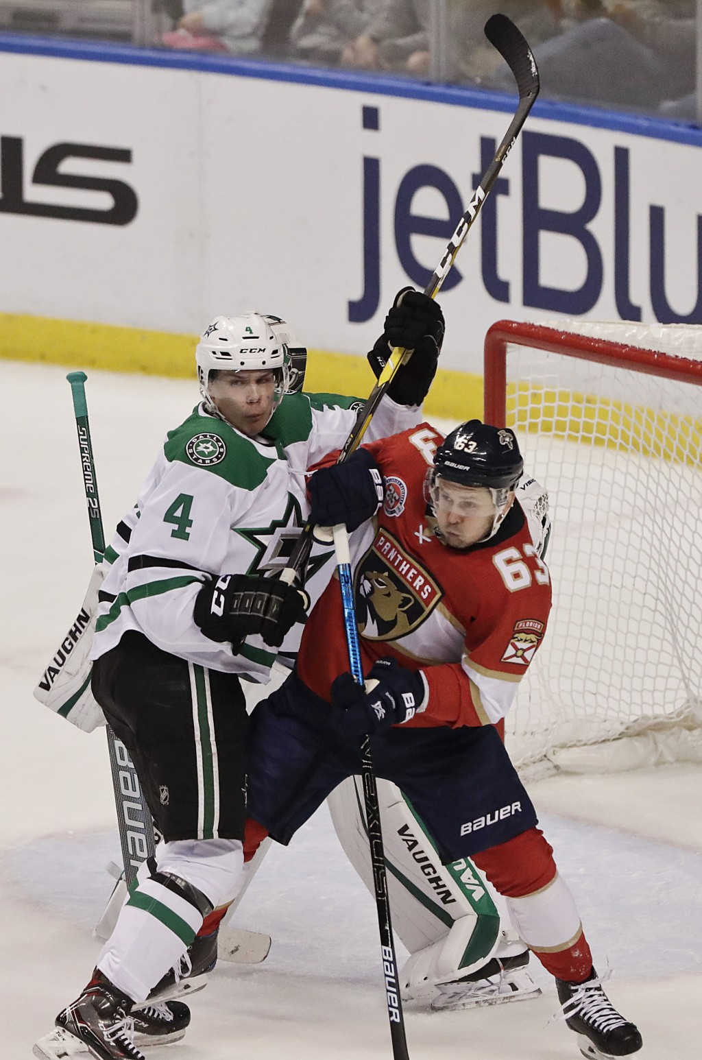 Dallas Stars defenseman Miro Heiskanen (4) and Florida Panthers right wing Evgenii Dadonov (63) battle during the second period of an NHL hockey game,...
