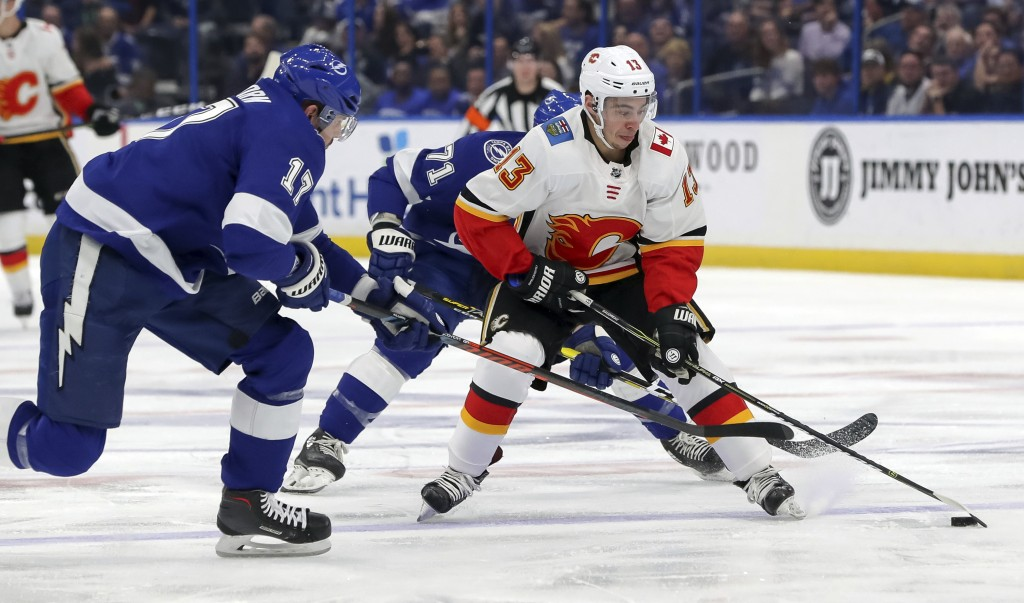 Calgary Flames' Johnny Gaudreau is checked by Tampa Bay Lightning's Alex Killorn during the first period of an NHL hockey game Tuesday, Feb. 12, 2019,