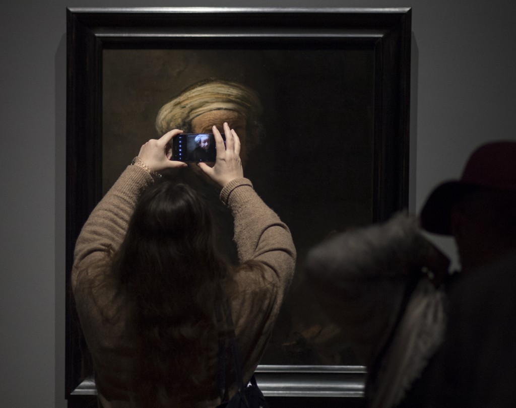 "A visitor takes images of Rembrandt's ""self-portrait as the Apostle Paul"" (oil on canvas, 1661) during a press preview of an exhibition of the all the"