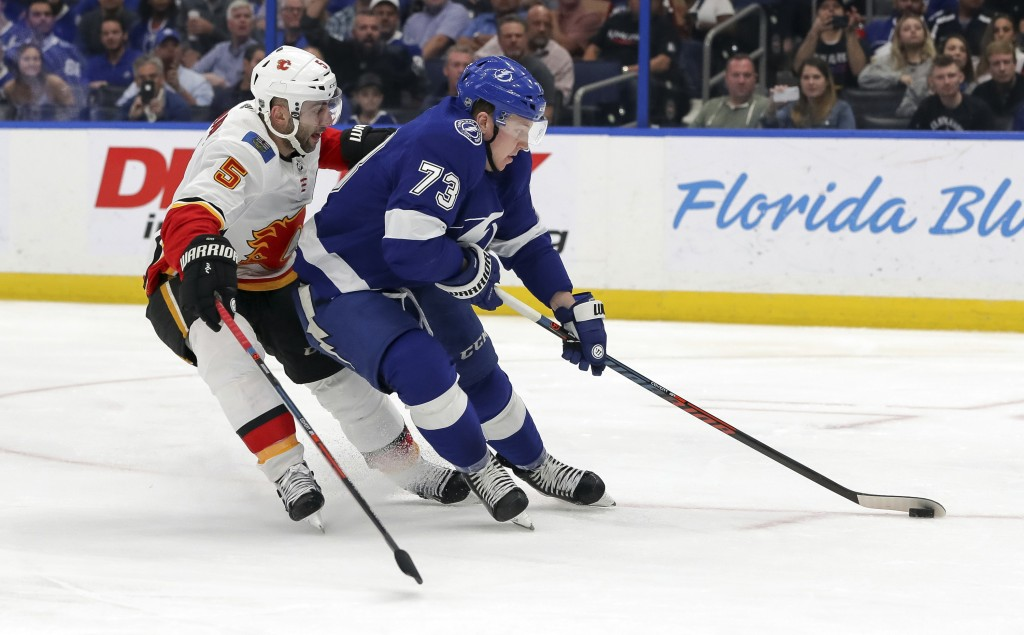 Tampa Bay Lightning's Adam Erne avoids the check of Calgary Flames' Mark Giordano during the second period of an NHL hockey game Tuesday, Feb. 12, 201...