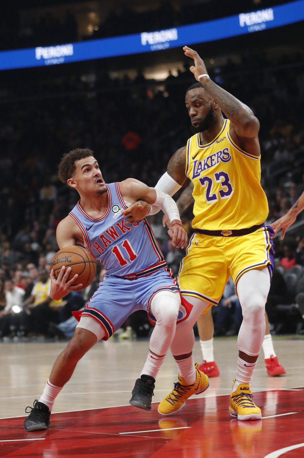 Atlanta Hawks guard Trae Young (11) drives against Los Angeles Lakers forward LeBron James (23) during the first half of an NBA basketball game Tuesda...