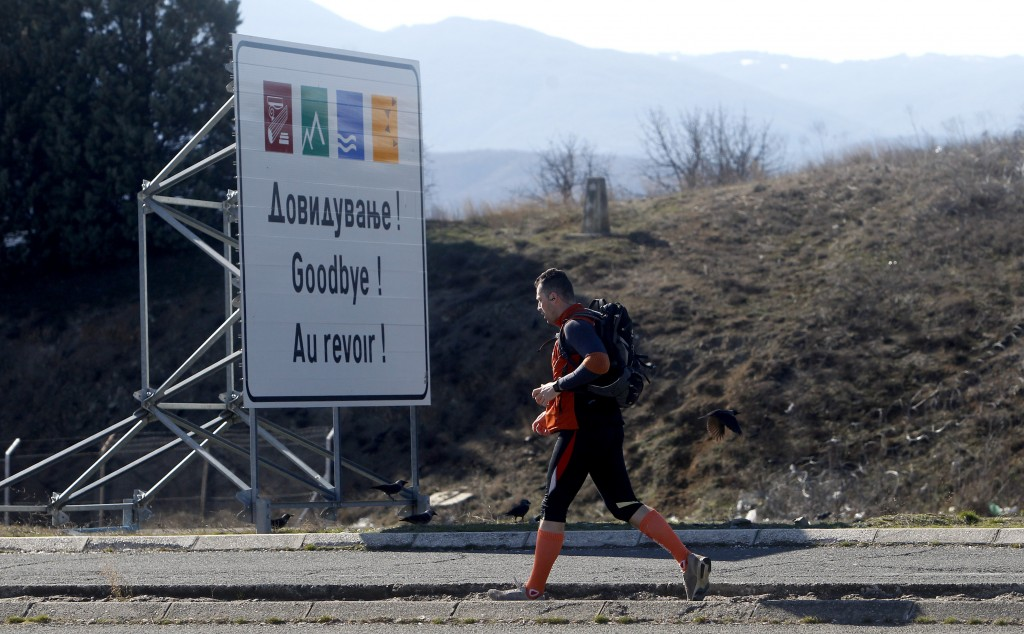 A man walks, leaving Macedonia and entering into Greece, at Bogorodica border crossing on Macedonia's southern border with Greece, Tuesday, Feb. 12, 2