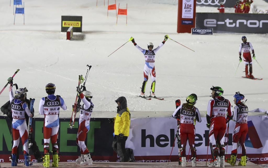 Switzerland's Ramon Zenhaeusern, center, celebrates as Switzerland wins the team event, at the alpine ski World Championships in Are, Sweden, Tuesday,