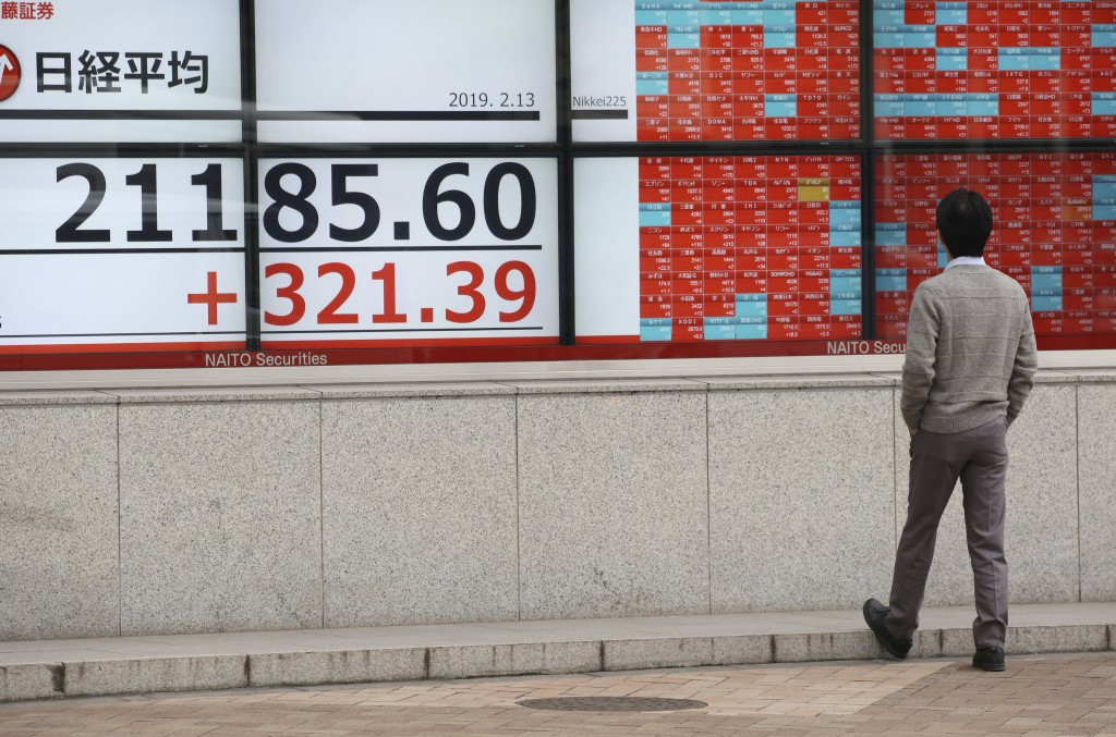 A man looks at an electronic stock board showing Nikkei Stock index, at a securities firm in Tokyo, Wednesday, Feb. 13, 2019.  Asian shares were mostl...