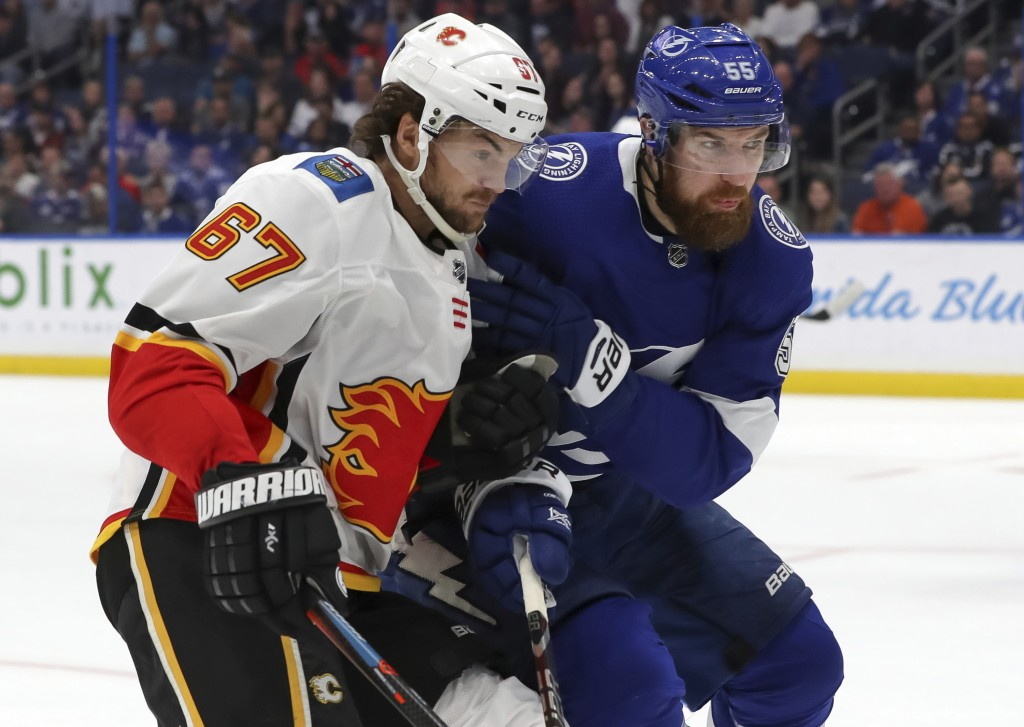 Calgary Flames' Michael Frolik, left, of the Czech Republic, goes into the boards for a loose puck against Tampa Bay Lightning's Braydon Coburn during...