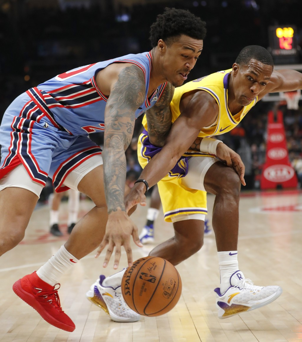 Los Angeles Lakers guard Rajon Rondo (9) reaches in to knock the ball away from Atlanta Hawks forward John Collins (20) during the first half of an NB...