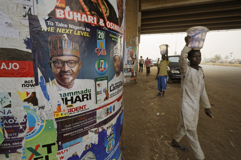 The face of incumbent President Muhammadu Buhari is seen on a campaign poster fixed to the pillars of a highway bridge near Nyanya, on the eastern out...