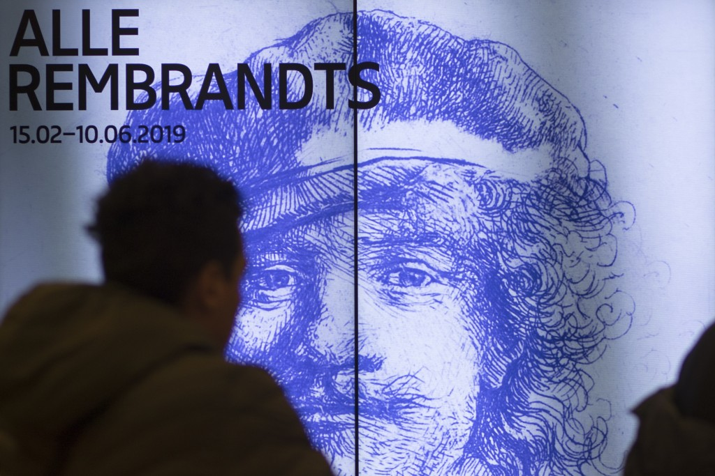 A visitor passes a billboard drawing attention to the exhibit of all the Rijksmuseum's Rembrandts in Amsterdam, Netherlands, Wednesday, Feb. 13, 2019....
