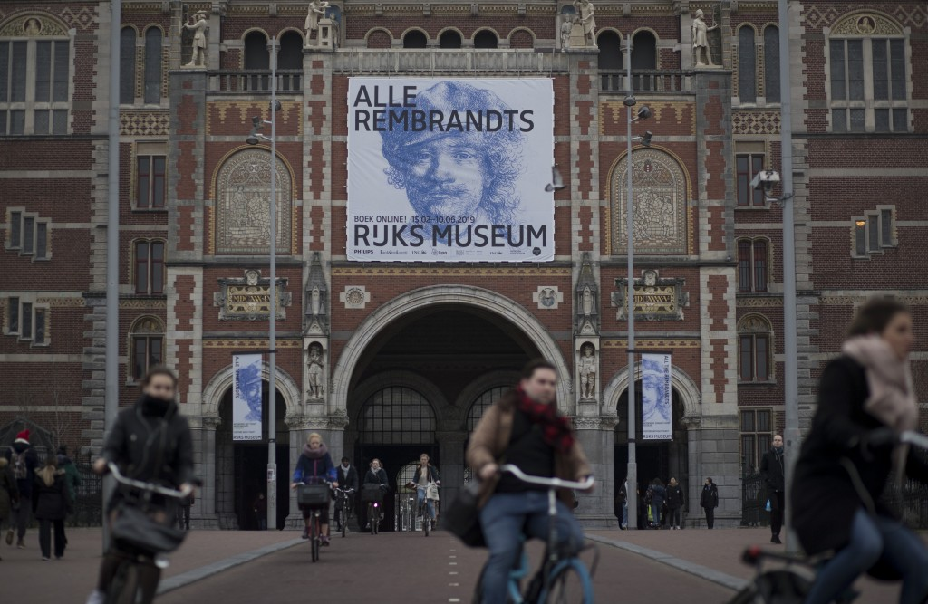 "Bicyclists pass through an underpass of the Rijksmuseum where a billboard reads ""All Rembrandts"" to draw attention to an exhibition of the all the Rij"