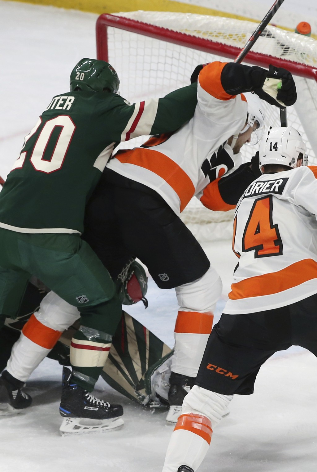 Philadelphia Flyers' James van Riemsdyk, right, is shoved by Minnesota Wild's Ryan Suter as he scores the go-ahead goal in the third period of an NHL