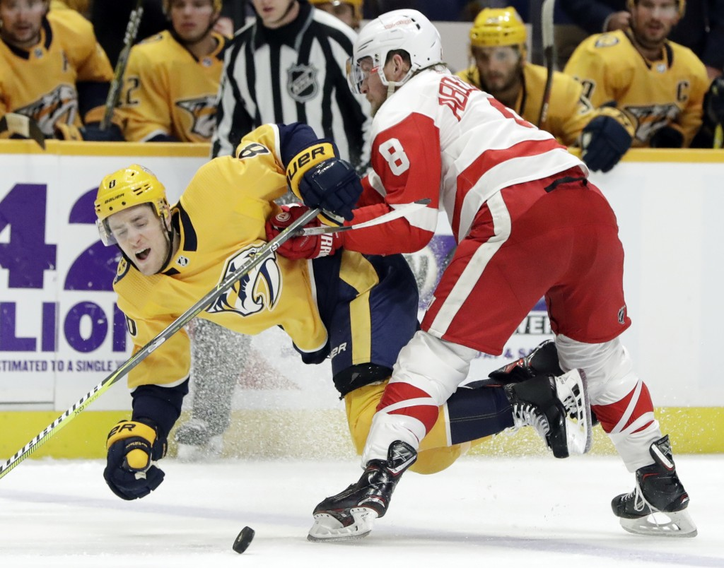 Detroit Red Wings left wing Justin Abdelkader, right, checks Nashville Predators center Kyle Turris off the puck during the second period of an NHL ho