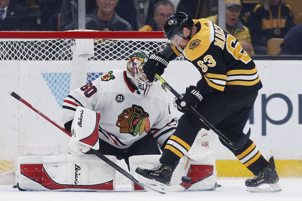 Boston Bruins' Brad Marchand (63) tries to get a shot on Chicago Blackhawks' Collin Delia (60) during the first period of an NHL hockey game in Boston...