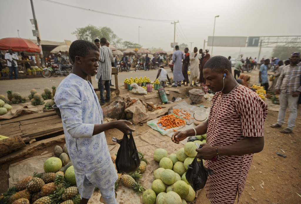 A customer, right, buys fruit from a street seller by the side of the road at a busy intersection near Nyanya, on the eastern outskirts of the capital...