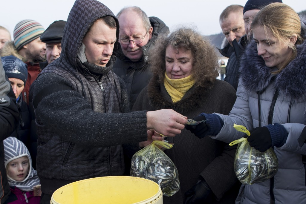 In this photo taken on Saturday, Feb. 9, 2019, a fisherman takes money as he sells a freshly caught smelt during a traditional winter smelt fish festi...