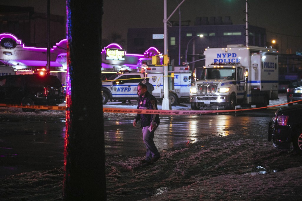Investigators look over the area after a few New York City police officers were shot while responding to a robbery at a T-Mobile store in the Queens b