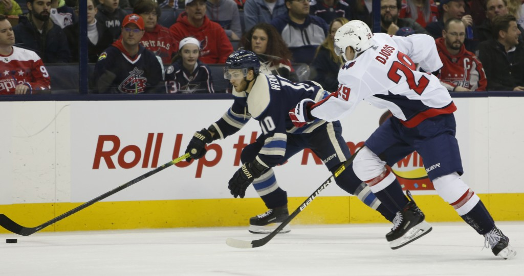 Columbus Blue Jackets' Alexander Wennberg, left, of Sweden, carries the puck up ice as Washington Capitals' Christian Djoos, of Sweden, defends during