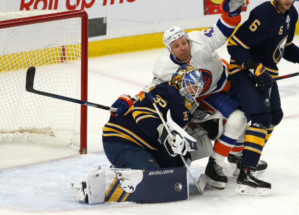 Buffalo Sabres goalie Linus Ullmark (35) and New York Islanders forward Leo Komarov (47) collide during the first period of an NHL hockey game, Tuesda...
