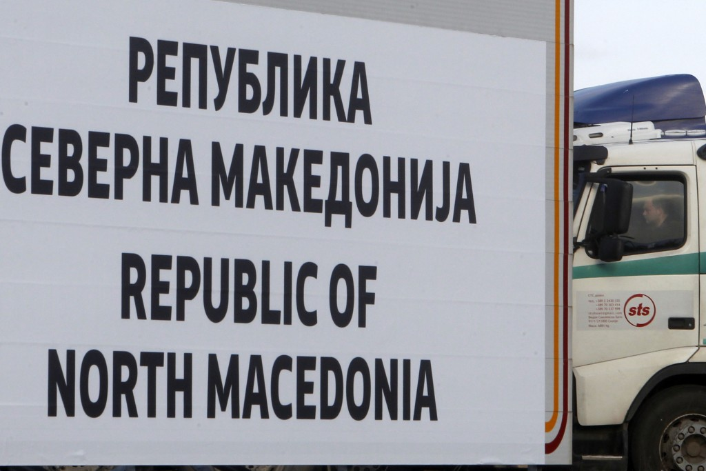 A truck driver waits behind a new road sign with the name Republic of North Macedonia in the southern border with Greece, near Gevgelija, Wednesday, F...