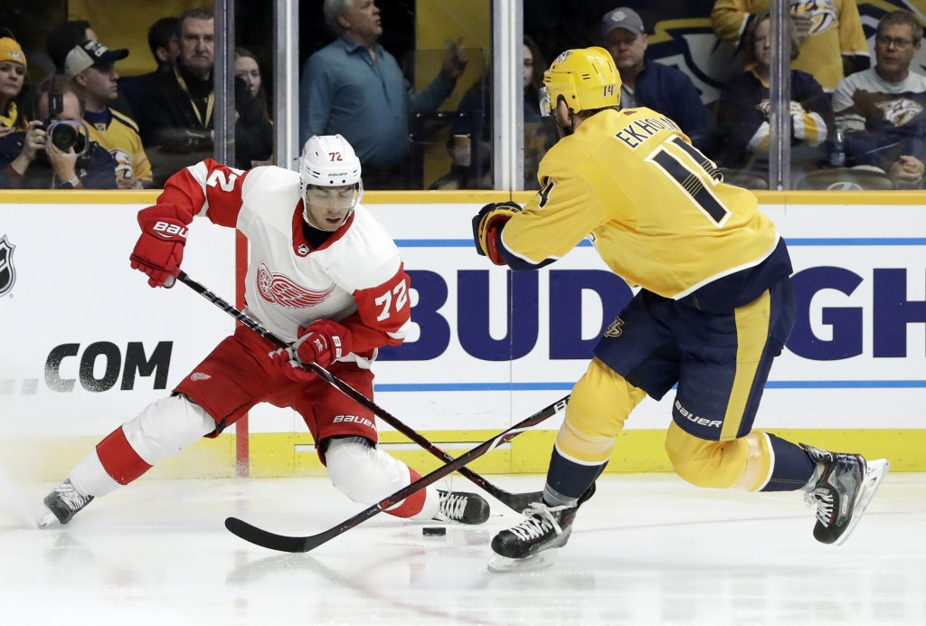 Detroit Red Wings center Andreas Athanasiou (72) moves the puck against Nashville Predators defenseman Mattias Ekholm (14), of Sweden, during the firs