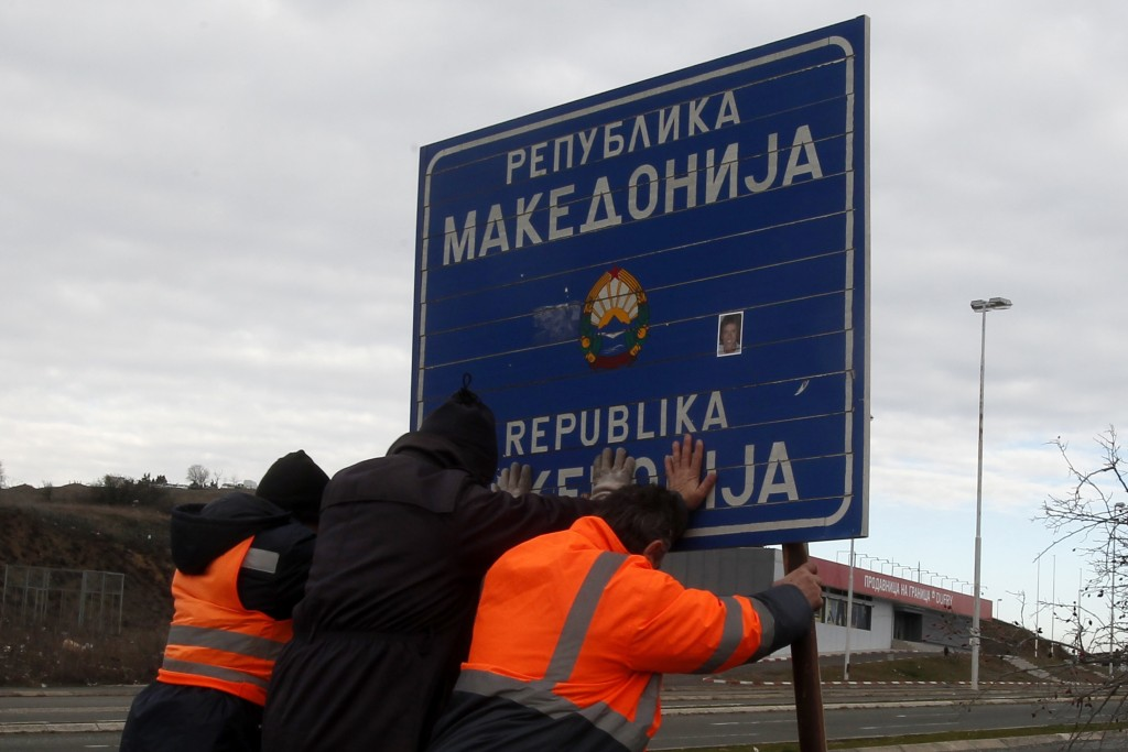 Workers remove a road sign that reads ''Republic of Macedonia'' in the southern border with Greece, near Gevgelija, Wednesday, Feb. 13, 2019. The smal