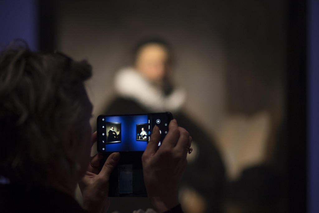 A guest takes pictures during a press preview of an exhibition of the all the Rijksmuseum's Rembrandts in Amsterdam, Netherlands, Wednesday, Feb. 13, ...