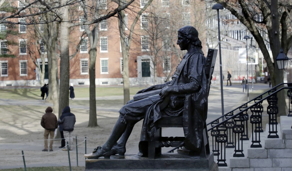 FILE - In this Dec. 13, 2018 file photo, the John Harvard statue looks over Harvard Yard at Harvard University in Cambridge, Mass. A final round of ar