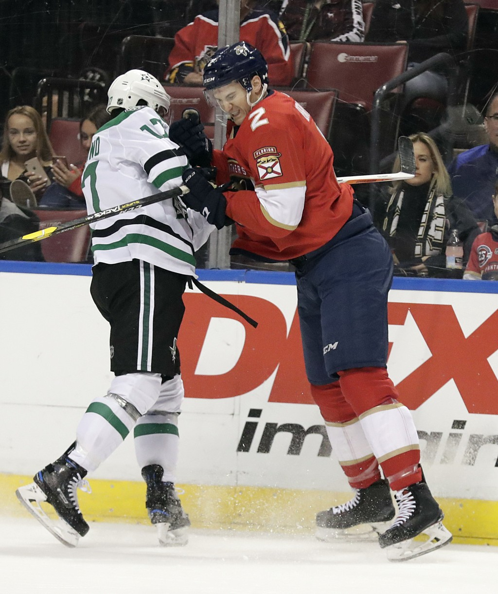Florida Panthers defenseman Josh Brown (2) and Dallas Stars center Andrew Cogliano (17) battle during the first period of an NHL hockey game on Tuesda...